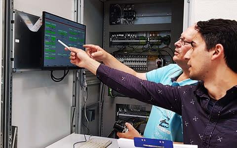 computer software human-machine interface monitor und zwei personen analysieren
