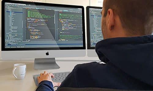 software entwickler vor einem bildschirm mit code zur entwicklung human-machine interface